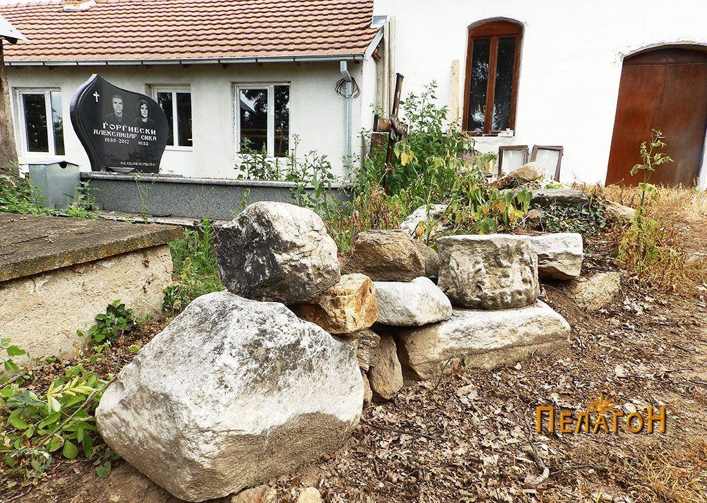 Куп споменици и камен од стара градба во дворот на црквата во Браилово