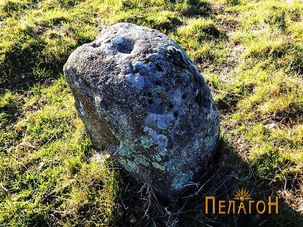 Камен во чиста површина со крушни мали јами и крст