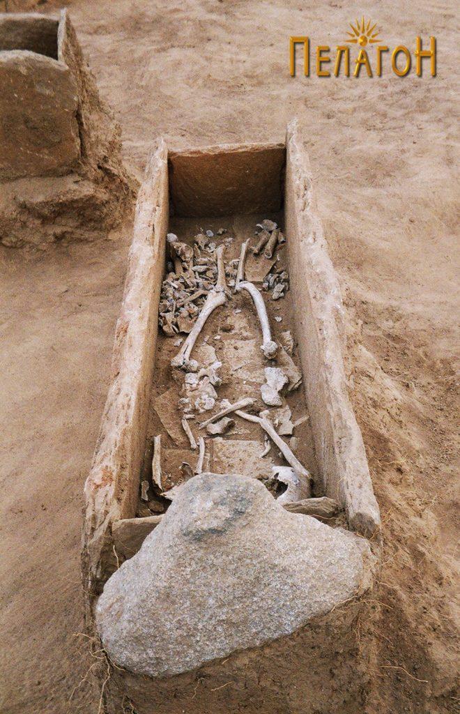 Отворен гроб обележан со триаголна камена фрома и со скелет во гробната јама